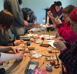 People around a table working with electronics components on prototype boards